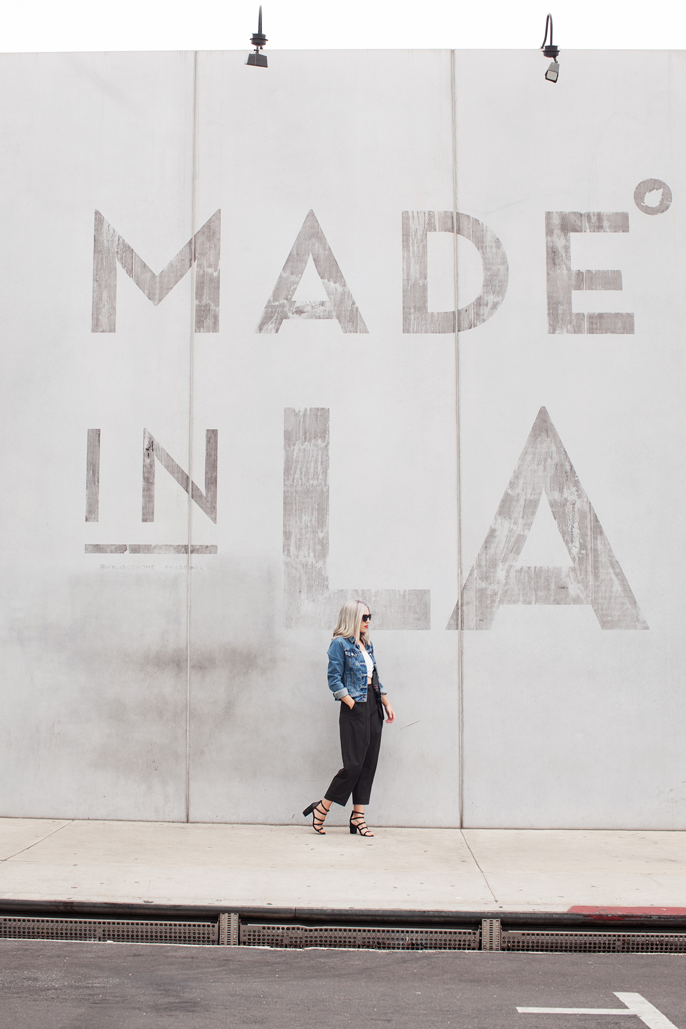 woman wearing denim jeans and black pants standing in front of a wall with text Made in LA for best boutiques in la