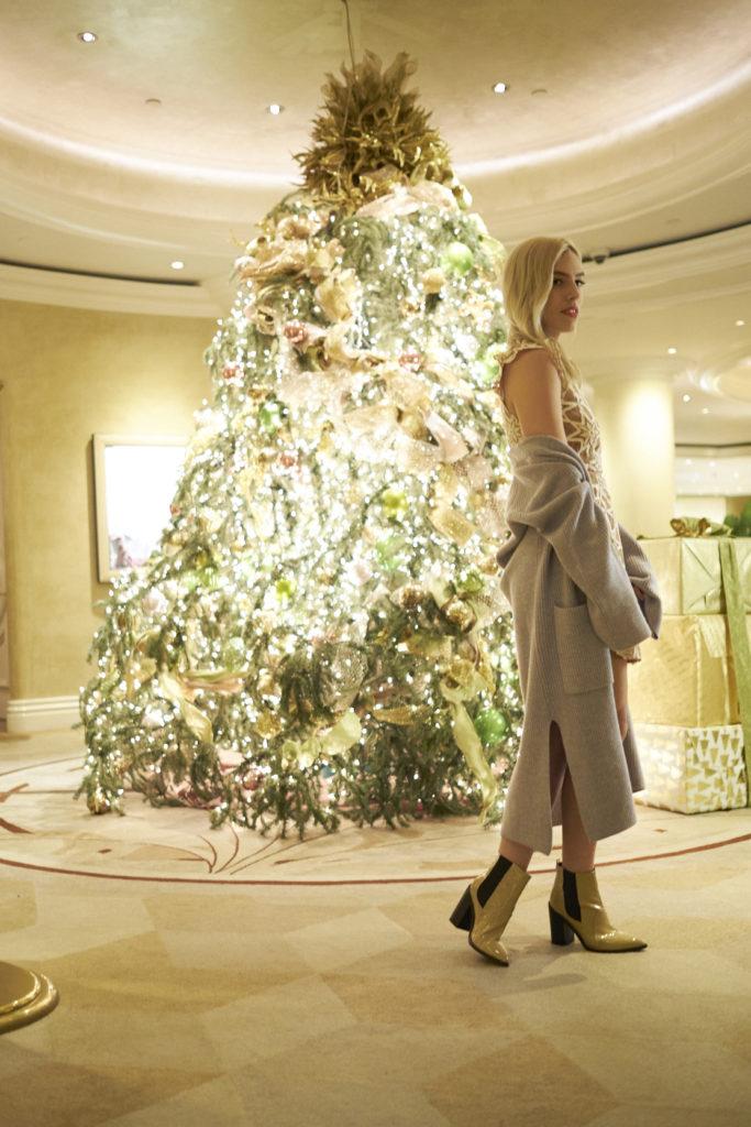 woman posing near a christmas tree and wearing fun holiday festive wear