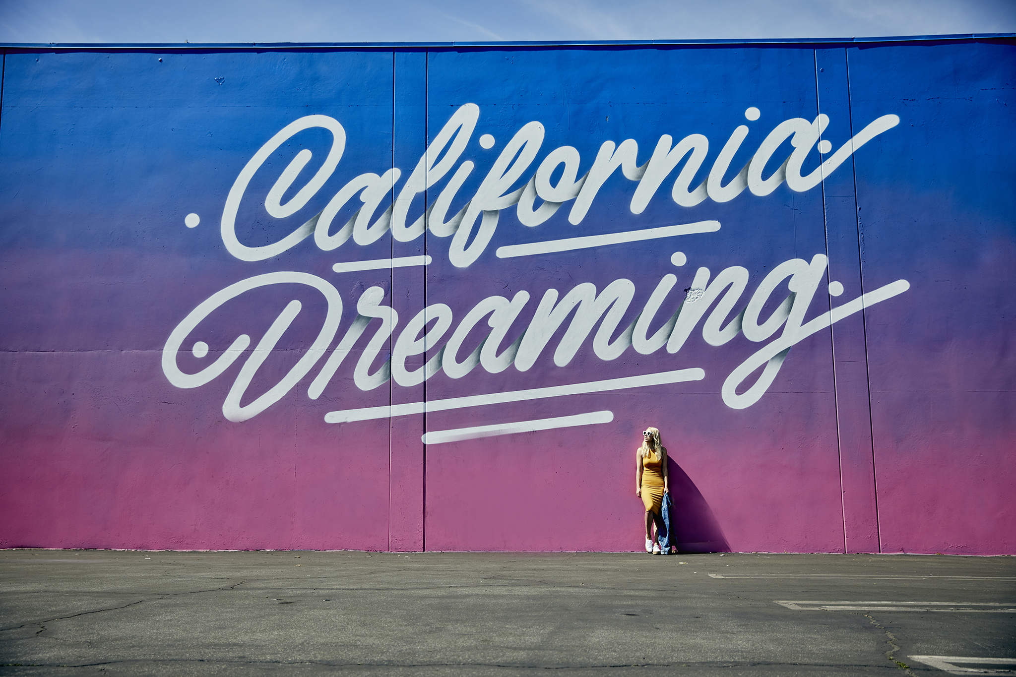 woman wearing yellow and taking her photo on one of the Spots To Take Photos In LA