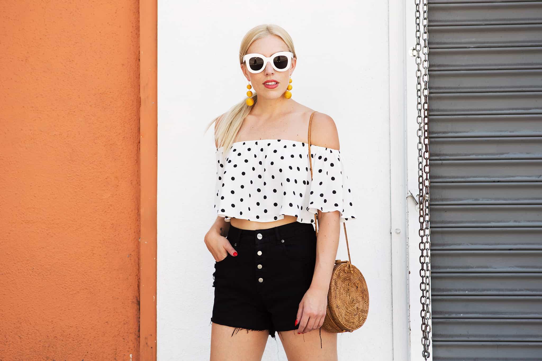 woman wearing white sunglasses, polka dots top, and denim shorts