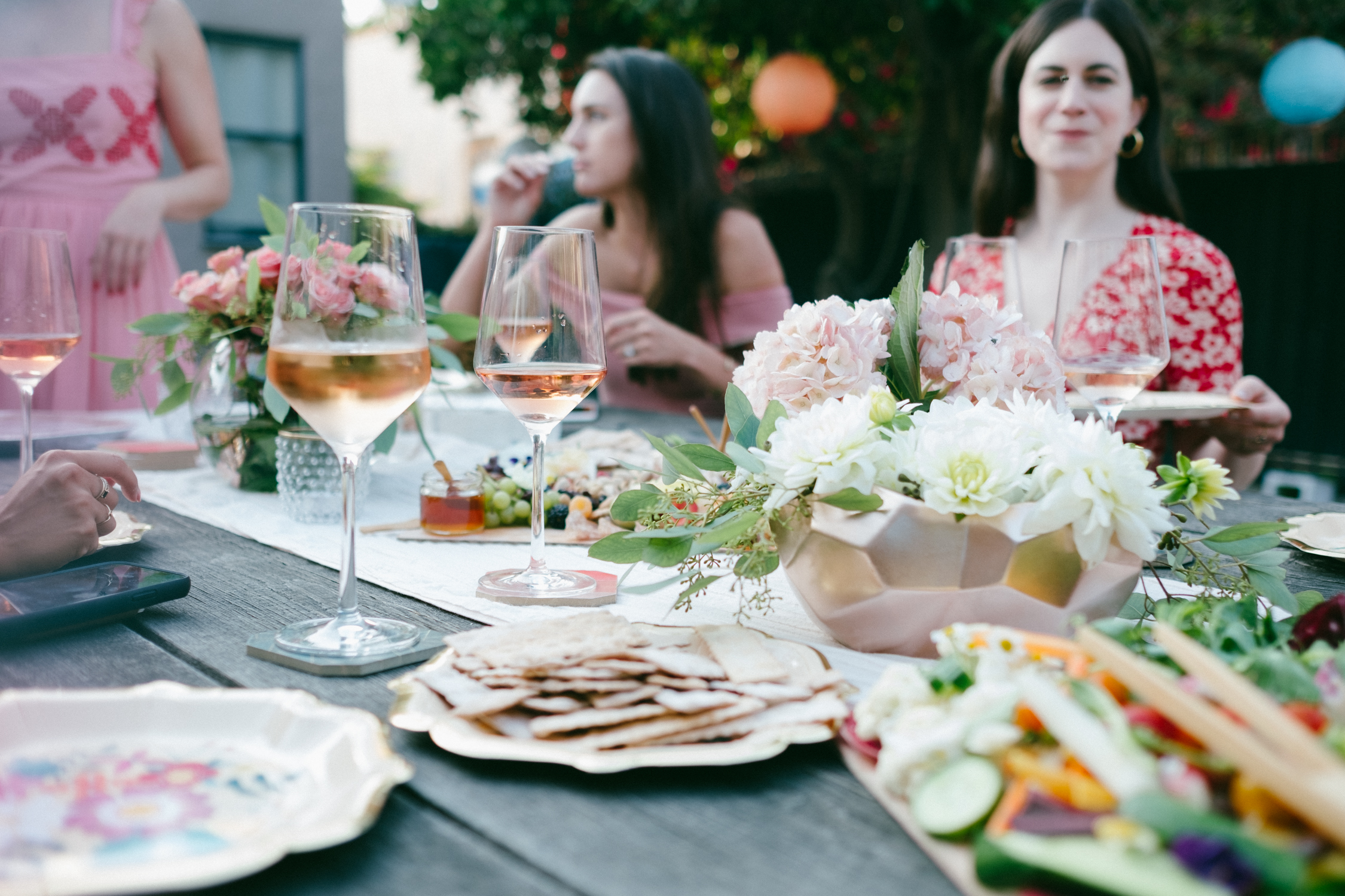 table with food and drinks and women sitting around it