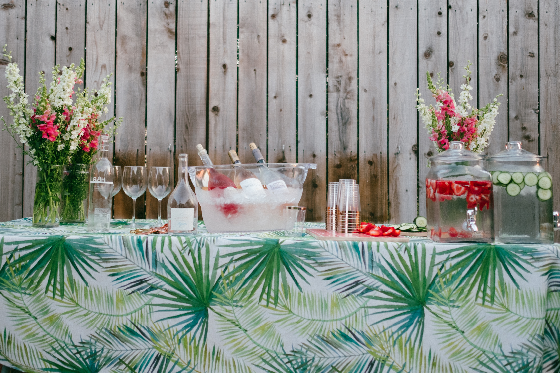 a table with flowers and different drinks for rosé all day cocktail party