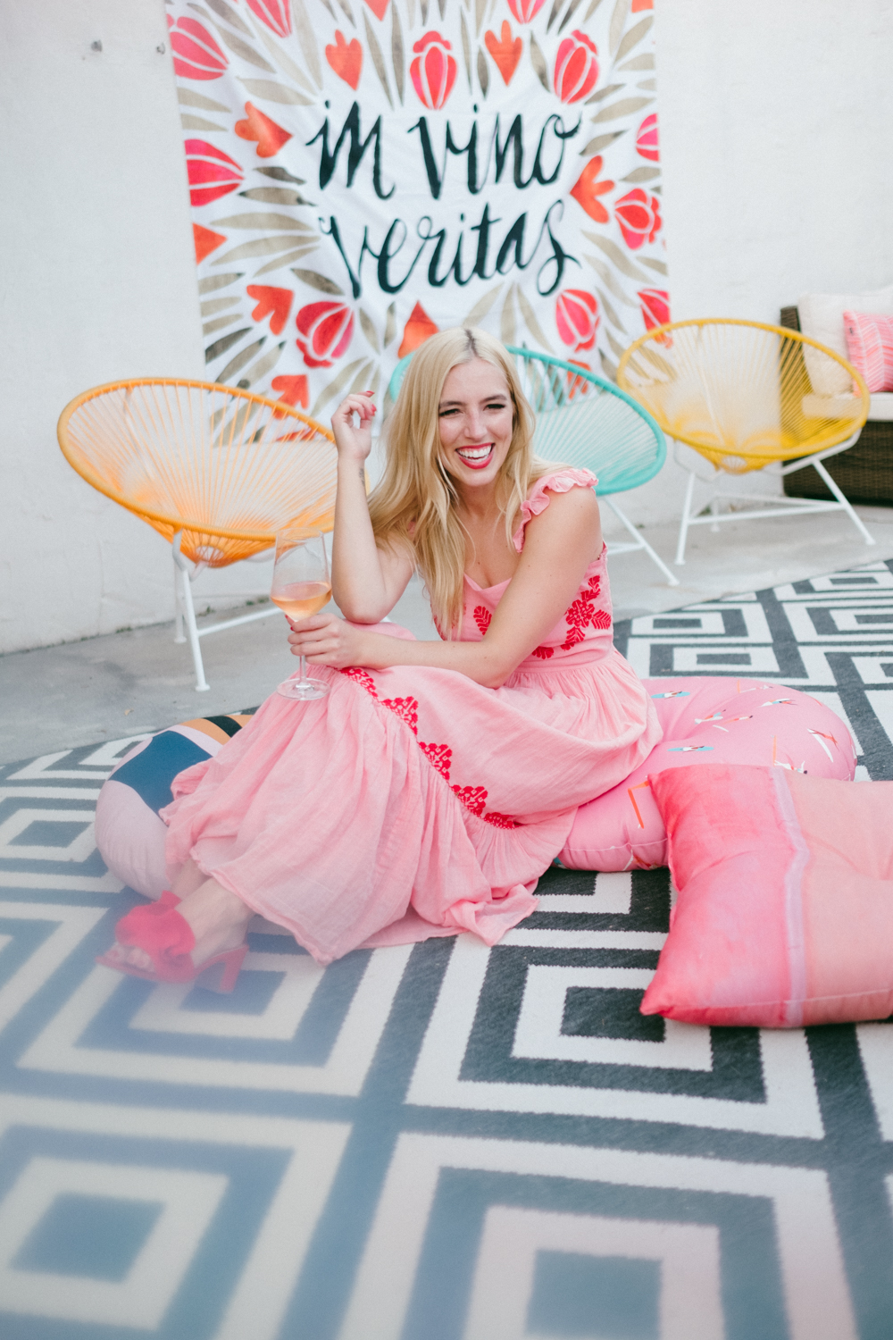 blonde woman wearing pink dress and sitting on the floor with pillows