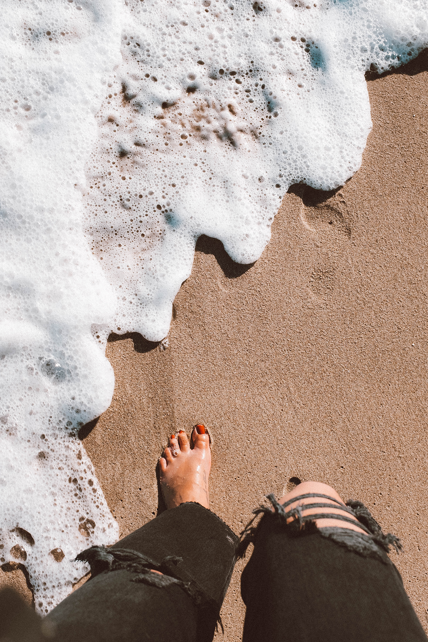 woman's feet stepping into the sand and spending the perfect day in malibu