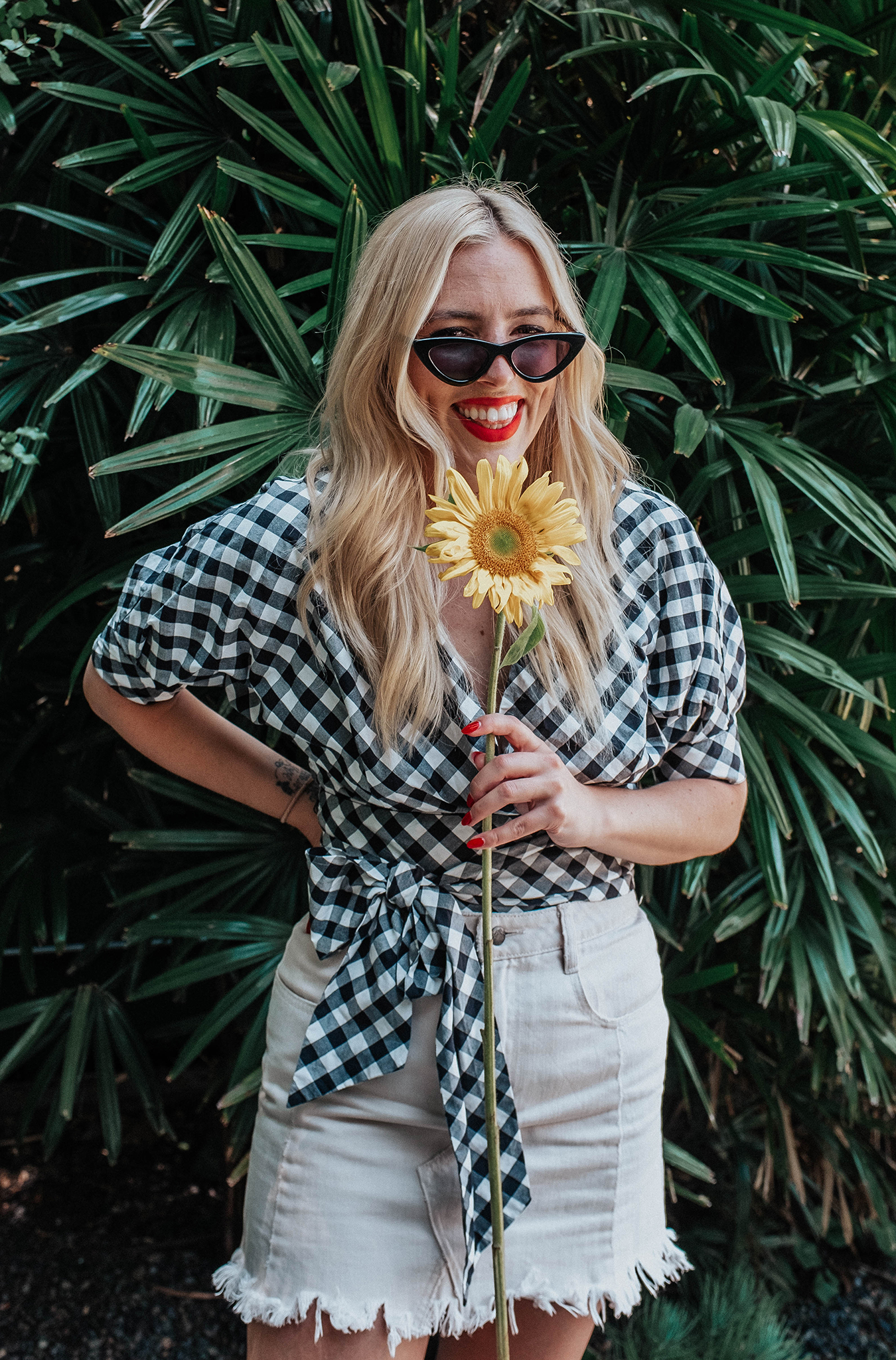 woman wearing gingham top with puff sleeves and white denim skirt while holding a sunflower