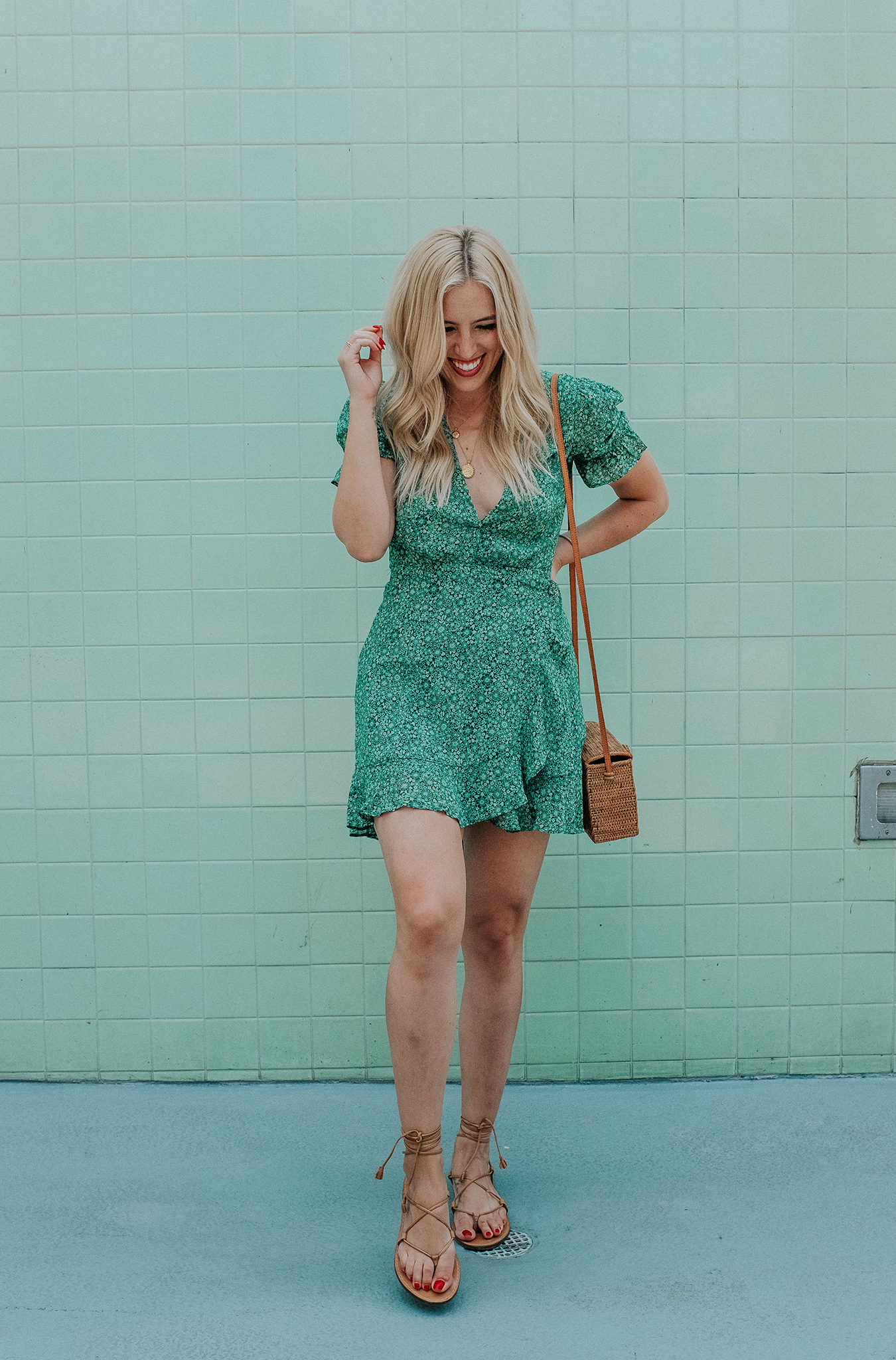 woman wearing green dress with puff sleeves, flat sandals, and sling bag